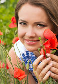 Beautiful woman with red spring flowers in a garden — Fotografia Stock