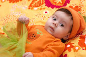 Cute little girl in orange clothes — Stock Photo