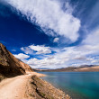 Road going along high mountain lake under blue sky — Stock Photo