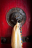 Old doorknob decorated with tassel — Stock Photo