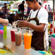 Thai man selling fresh juice at market - Stock Photo