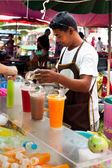 Thai man selling fresh juice at market — Stock Photo