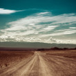 Empty rural road going through prairie under cloudy sky — Stock Photo #28662971