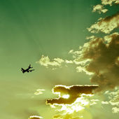 Airplane silhouette in beautiful cloudy sunset sky — Stock Photo