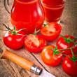 Tomato juice in glass jar and fresh organic tomatoes — Stock Photo