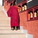 Buddhist monk rotating praying wheel. — Stock Photo