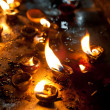 Stock Photo: Burning oil lamps at religious temple