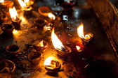 Burning oil lamps at religious temple — Stock Photo