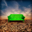 Ecology and global warming concept. Grassy sofa standing at cracked desert landscape — Stock Photo #43240617