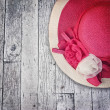 Pink summer hat with silk roses flowers at grunge wooden texture — Stock Photo