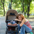 Young mother with perambulator — Stock Photo