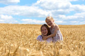 Young girls joys on the wheat field — Stock Photo