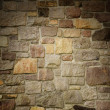 Stock Photo: Masonry Wall of Multicolored Stone Lit Dramatically