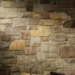 Stock Photo: Masonry Wall of Multicolored Stone Lit Diagonally