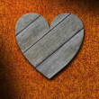 Weathered gray wood heart against rusty metal background — Stock Photo