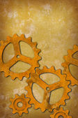 Rusty gears against a mottled yellowish background — Zdjęcie stockowe