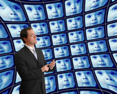 Man in suit monitoring babies on distorted video screens — Stock Photo