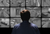 Security guard conducting surveillance by watching several secur — Stock Photo