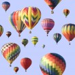 A group of colorful hot-air balloons floating across a blue sky — Stock Photo