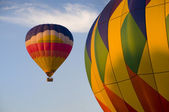 Airborne hot-air balloon with another in foreground — Stock Photo