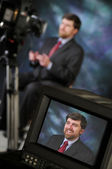 Monitor in studio showing man talking to video camera — Stock Photo