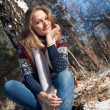 Girl in winter forest sits under a birch — Stock Photo