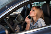 Emotional blonde behind the wheel lipstick — Stock Photo