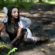 Girl with angel wings lying in the mud — Stock Photo