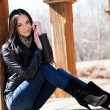 Stock Photo: Young brunette womsitting leaning against wooden post