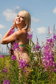 Beautiful young blonde woman among wildflowers — Stock Photo