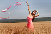 Girl in the field with a gymnastic ribbon — Stock Photo