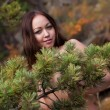 Beautiful young girl in the autumn coniferous forest — Stock Photo