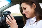 快乐的女孩在相机上看照片,坐在车里 — 图库照片