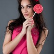 Girl in a pink dress holding a lollipop — Stock Photo #37206789