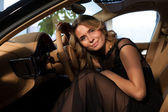 Blonde at the wheel of an expensive car — Stock Photo