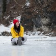 Stock Photo: Girl sitting on the ice among the rocks
