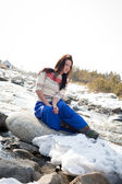 Young girl sitting on the bank of the river snow — Stock Photo