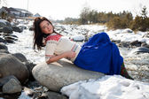 Young girl sitting on the bank of the river snow — Foto Stock