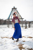 Young girl in a long skirt on a background of a winter forest — Stock Photo
