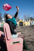 Cheerful girl with a balloon sitting on a bench — Stock Photo