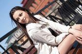 Junge geschäftsfrau, die auf einer bank in der stadt — Stockfoto