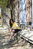 Business woman on the background of an old wooden house in the early twentieth century — Stock Photo