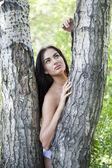 Загорелая девушка прислонилась ствол дерева — Стоковое фото