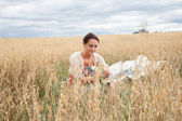 Girl sitting in a field of wheat ears — Photo