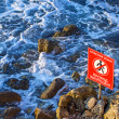 Danger! No walking sign on the rocky sea coast — Stok fotoğraf
