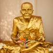 Gold buddhist monk statue - Stock Photo