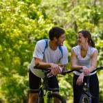 Happy couple ridine bicycle outdoors — Stock Photo #12522600