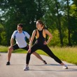 Couple doing stretching exercise  after jogging — ストック写真