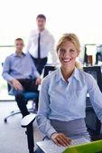 Zakenvrouw met haar personeel op achtergrond op kantoor — Stockfoto