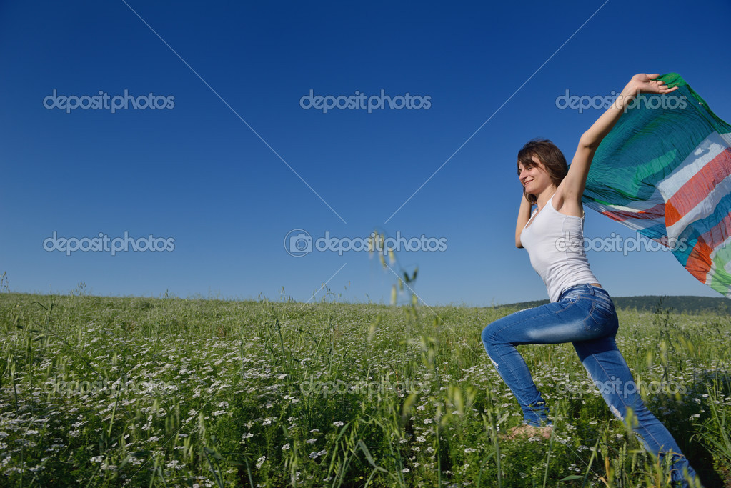 Young woman standing jumping and running  on a wheat field with blue sky in  background at summer day representing healthy life and agriculture concept — Stock Photo #13119980